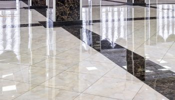 Marble floor in the luxury lobby of office or hotel. Real floor tile pattern with reflections for background. Shiny floor after professional cleaning.